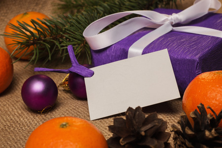 happy holidays: Purple gift with postcard, orange tangerines, fir-cones, Christmas decorations and fur-tree branch Stock Photo