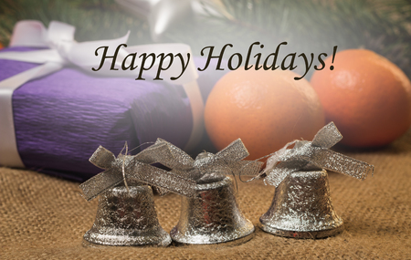 silver bells: Tag Happy Holidays, silver bells and fur-tree branch, purple gift, orange tangerines, fir-cones