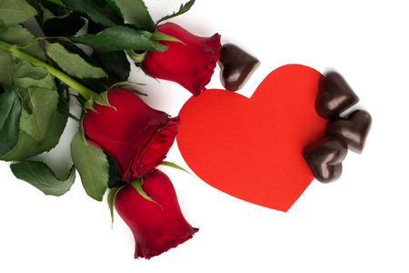 Blumenstrauß von roten Rosen, von rotem Papierherzen und von Süßigkeiten in einer Form eines Herzens lokalisiert auf weißem Hintergrund Standard-Bild - 51626419