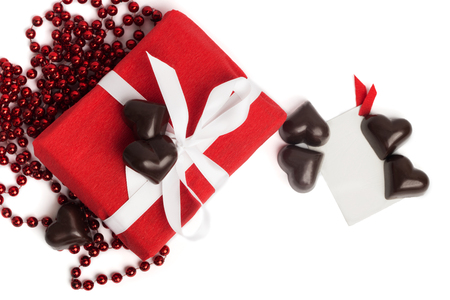 felicitaciones cumplea�os: Red present box with white ribbon, candies in a shape of a heart and postcard isolated on white background