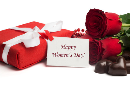 felicitaciones cumplea�os: Tag Happy Womens Day with red present box and white ribbon, red roses and candies in a shape of a heart isolated on white background Foto de archivo