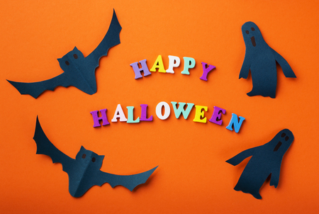 Halloween holiday background with paper bats, ghosts and text happy halloween. View from above