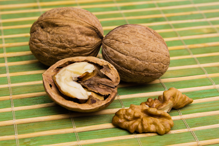 Group of walnuts and splintered walnut with heart-shaped core on green background. Walnuts close up. Healthy organic food concept. Stock Photo
