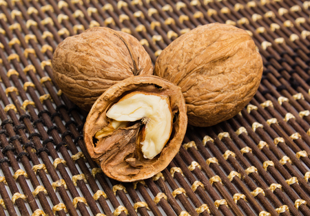 Group of walnuts and splintered walnut with heart-shaped core on brown background. Walnuts close up. Healthy organic food concept.