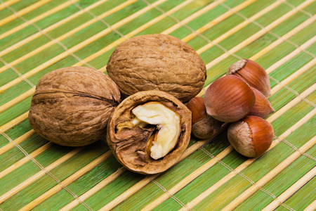 Group of hazelnuts, walnuts and splintered walnut with heart-shaped core on green background. Walnuts close up. Healthy organic food concept.