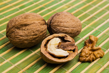 Group of walnuts and splintered walnut with heart-shaped core on green background. Walnuts close up. Healthy organic food concept. Stok Fotoğraf
