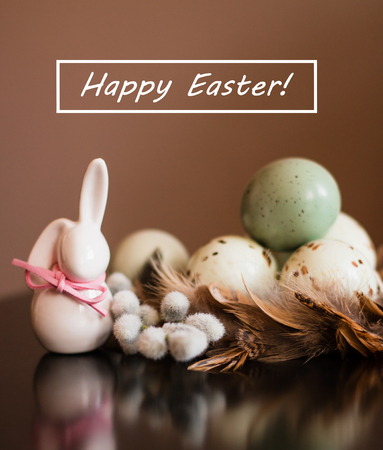 Small white rabbit figurine with easter eggs, willow branch and feathers on pastel background with text Happy Easter 스톡 콘텐츠