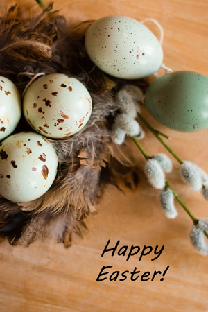 Easter eggs, willow branch and feathers' nest on wooden background with text happy easter. View from above. Holiday background. 스톡 콘텐츠