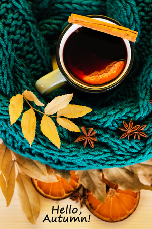 Autumn, fall leaves, hot steaming cup of glint wine and a warm blue scarf on wooden table background. Seasonal, autumnal hot wine, Autumn relaxing and still life concept with text hello autumn. Top view.