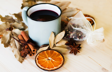 Autumn, fall leaves, hot steaming cup of glint wine on wooden table background. Seasonal, autumnal hot wine, Autumn relaxing and still life concept. Banco de Imagens