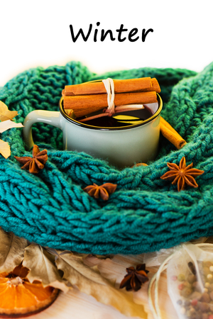 Winter, fall leaves, hot steaming cup of glint wine and a warm blue scarf on wooden table background. Seasonal, winter hot wine, Winter relaxing and still life concept. Text winter. Banco de Imagens