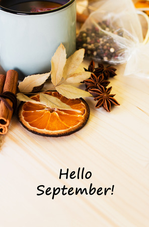 Autumn, fall leaves, hot steaming cup of glint wine on wooden table background. Seasonal, autumnal hot wine, Autumn relaxing and still life concept. Top view with text hello september.