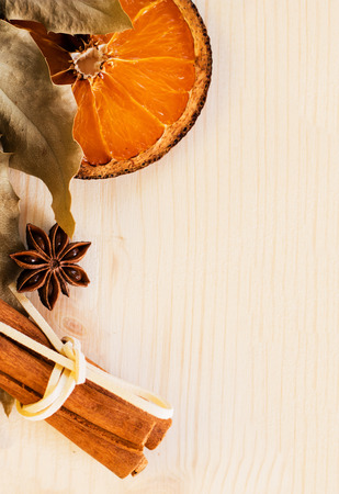 Anise, cinnamon and orange ingredients for preparation mulled wine, closeup on wooden background.Top view flat lay copy space.