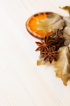 Anise, orange and dry leaves ingredients for preparation mulled wine, closeup on wooden background.Top view flat lay copy space. Banco de Imagens
