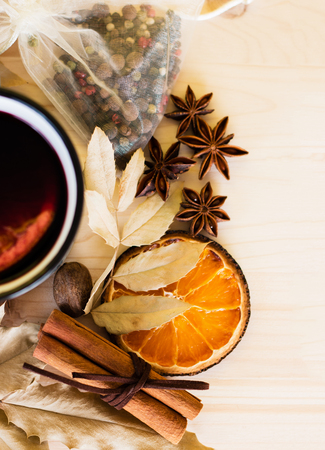 Autumn, fall leaves, hot steaming cup of glint wine on wooden table background. Seasonal, autumnal hot wine, Autumn relaxing and still life concept. Top view.