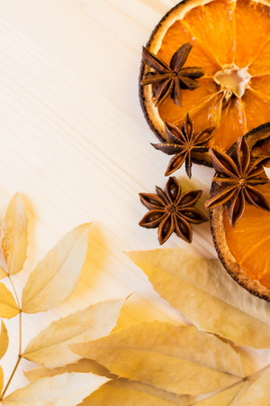 Anise, dry leaves and orange ingredients for preparation mulled wine, closeup on wooden background.Top view flat lay copy space.
