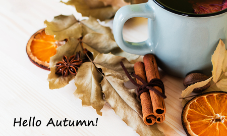 Autumn, fall leaves, hot steaming cup of glint wine on wooden table background. Seasonal, autumnal hot wine, Autumn relaxing and still life concept. Top view with text hello autumn. Imagens
