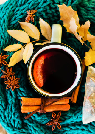 Autumn, fall leaves, hot steaming cup of glint wine and a warm blue scarf on wooden table background. Seasonal, autumnal hot wine, Autumn relaxing and still life concept. Top view.