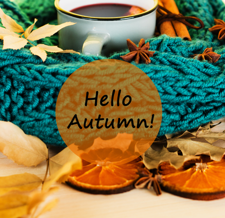 Autumn, fall leaves, hot steaming cup of glint wine and a warm blue scarf on wooden table background. Seasonal, autumnal hot wine, Autumn relaxing and still life concept with text hello autumn.