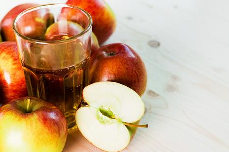 Vaso de sidra de manzana fresca y media manzana cerca de manzanas de otoño. Fondo de madera, espacio para texto. Fondo otoñal.