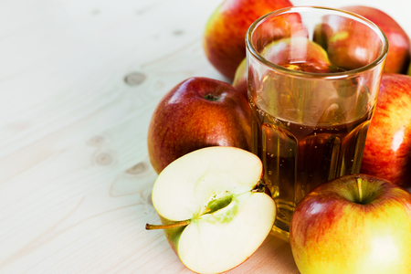 Glass of fresh apple cider and half apple near autumn apples. Wooden background, space for text. Autumnal background.