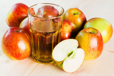 Glass of fresh apple cider and half apple near autumn apples. Wooden background. Autumnal background.