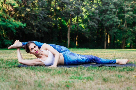 Slim young woman practicing stretching in nature. Lying on green grass with an elongated leg. Green background. Good healthy and sport concept. Archivio Fotografico