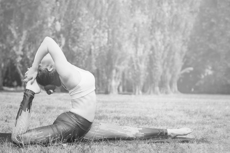 Slim young woman practicing yoga in nature, standing in deep stretching exercise, Good healthy and sport concept. Copy space for text. Black and white photo.