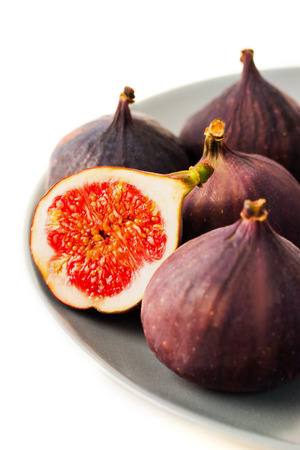 Fresh figs on grey plate. Fruit with half isolated on white background. With clipping path.