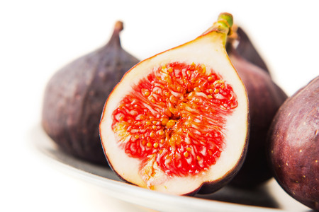 Fresh figs on grey plate. Fruit with half isolated on white background. With clipping path. Copy space for text. 版權商用圖片
