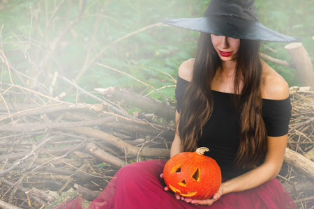 Halloween holiday background. Halloween Witch with a halloween pumpkin jack o lantern decor with funny face in a dark forest with toned effect. Beautiful young woman in witches hat and costume.