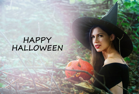 Halloween holiday background. Halloween Witch with a halloween pumpkin jack o lantern decor with funny face in a dark forest with toned effect. Beautiful young woman in witches hat and costume holding pumpkin with text Happy Halloween Imagens