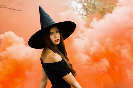 Halloween holiday background. Halloween Witch in a dark forest. Beautiful young woman in witches hat and costume on orange smoke background.