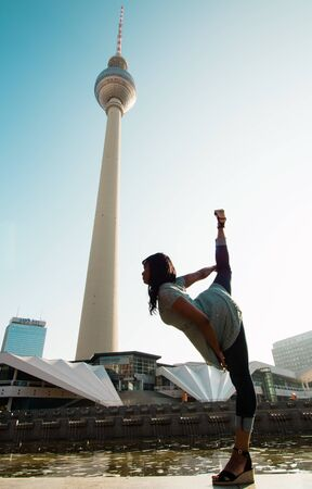 Berlin, Germany 09.09.18. View of TV tower in Berlin from the bottom on blue sky background with black dancing woman in front of it.