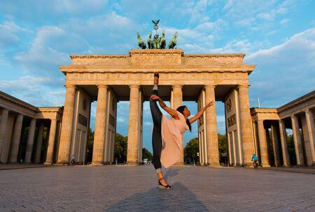 Berlin, Germany - 06.09.2018. Famous Brandenburger Tor (Brandenburg Gate) in beautiful golden morning light at sunrise with a black nice dancing woman.