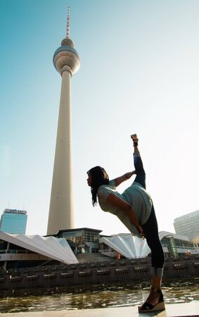 Berlin, Germany 09.09.18. View of TV tower in Berlin from the bottom on blue sky background with black dancing woman in front of it. 版權商用圖片 - 142313869