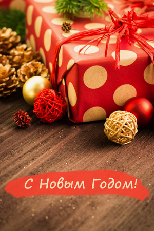 Christmas and New Year's Day festive decoration, golden ball, golden fir cones with present wrapped in red paper with golden circles on brown wood background with text Happy New Year (in russian Happy New Year)  on red.