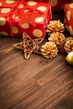 Christmas and New Year's Day festive decoration, golden ball, golden fir cones and wooden star with two presents wrapped in red paper with golden circles on brown wood background. View from above. Copy space for text. Banco de Imagens