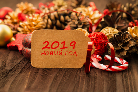 New Year's Day decoration, balls, fir cones, candies and stars with present wrapped in red paper with golden circles on wood background with text 2019 New Year (translation in russian 2019 New Year).
