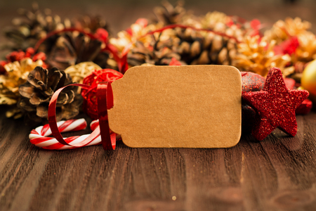 Christmas and New Year's Day decoration, golden balls and fir cones, red stars and candies with present wrapped in red paper with golden circles on wood background. Tag for text. Stock Photo