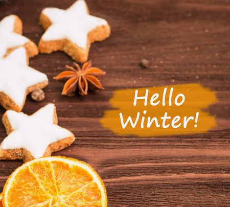 Winter and New Year theme. Spices, orange, cinnamon, anise, cookies in a shape of star, pepper on wooden background. Copy space for text. View from above with text hello winter. Stock Photo