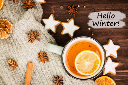 Winter theme. Hot tea with spices, orange, cinnamon, anise, cookies in a shape of star, pepper and gray scarf on wooden background. Flat lay, View from above with text hello Winter.