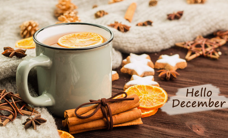 Winter theme. Cup of hot tea with spices, orange, cinnamon, anise, cookies in a shape of star, fir cones, pepper and gray scarf on wooden background with text hello december.