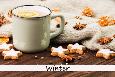 Winter theme. Cup of hot tea with spices, orange, cinnamon, anise, cookies in a shape of star, fir cones, pepper and gray scarf on wooden background with text Winter.