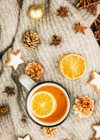 Winter and New Year theme. Christmas tea with spices, cup of tea with orange, cinnamon, anise, cookies in a shape of star, fir cones, pepper on gray scarf. Flat lay, View from above.