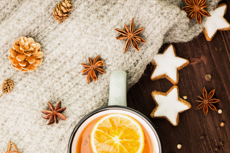 Winter theme. Christmas tea with spices, cup of tea with orange, cinnamon, anise, cookies in a shape of star, pepper, fir cones and gray scarf on wooden background. Flat lay, View from above.