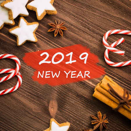 Christmas theme. Spices, cinnamon, anise, cookies in a shape of star, red candies, pepper on wooden background. View from above. Flat lay with text 2019 New Year.