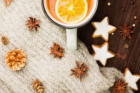 Winter theme. Christmas tea with spices, cup of tea with orange, cinnamon, anise, cookies in a shape of star, pepper and gray scarf on wooden background. Flat lay, View from above.