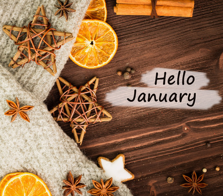 Winter theme. Spices, orange, cinnamon, anise, cookies in a shape of star, pepper, wooden stars and gray scarf on wooden background. View from above. Flat lay with text hello January.