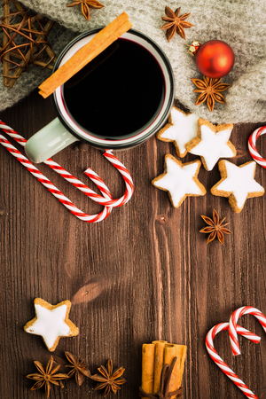 Christmas hot steaming cup of glint wine with spices, cinnamon, anise, cookies in a shape of star, red candies, pepper and gray scarf on wooden background. Copy space for text. View from above. Flat lay.